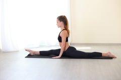 Donna che allunga le gambe nella posizione di spaccature nella stanza luminosa immagini stock