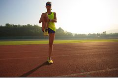 donna che allunga le gambe prima del funzionamento nel corso della mattinata soleggiata sullo stadio Fotografia Stock Libera da Diritti