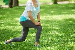 Donna che allunga le gambe su prato inglese verde Fotografia Stock