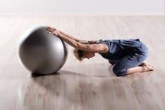Donna che allunga le spalle con la palla di forma fisica Fotografia Stock