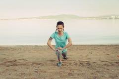 Donna che allunga le sue gambe prima dell'correre sulla spiaggia Fotografie Stock