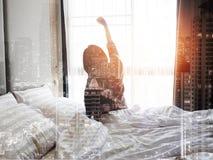 Donna che allunga a letto dopo avere svegliato, vista posteriore Immagini Stock