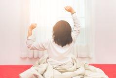 Donna che allunga a letto dopo avere svegliato, vista posteriore Fotografia Stock