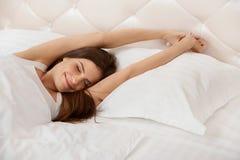 Donna che allunga nel suo letto Una ragazza che sveglia di mattina Immagini Stock