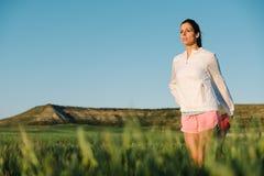 Donna che allunga per correre all'aperto Fotografie Stock