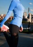 Donna che allunga prima della forma fisica nella vista Manhattan del parco Fotografia Stock Libera da Diritti