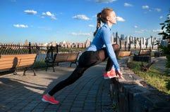Donna che allunga prima della forma fisica nella vista Manhattan del parco Immagine Stock Libera da Diritti