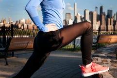 Donna che allunga prima della forma fisica nella vista Manhattan del parco Fotografie Stock Libere da Diritti