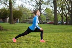 Donna che allunga prima della forma fisica in parco Fotografia Stock