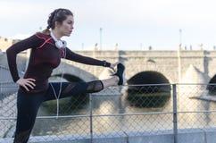 Donna che allunga riposo dopo avere corso e pareggiato in un parco con gli abiti sportivi Fotografia Stock