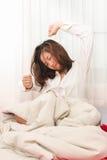 Donna che allunga sul letto dopo avere svegliato Fotografie Stock