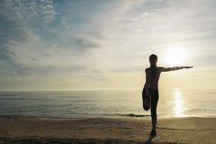 Donna che allunga sulla spiaggia Fotografie Stock