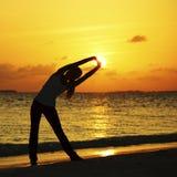 Donna che allunga sulla spiaggia di tramonto Fotografia Stock Libera da Diritti