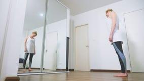 Donna che allunga vicino allo specchio al suo appartamento Il concetto di uno stile di vita sano, non uno sport professionale video d archivio
