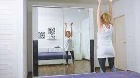 Donna che allunga vicino allo specchio al suo appartamento Il concetto di uno stile di vita sano, non uno sport professionale archivi video