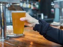 Donna che alza il vetro della pinta della birra di IPA in una barra fotografie stock libere da diritti