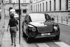 Donna che ammira Bentley Bentayga Hybrid di lusso SUV Fotografie Stock Libere da Diritti