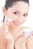 Donna che applica crema al suo fronte Fotografia Stock