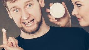 Donna che applica crema al suo fronte dell'uomo fotografia stock libera da diritti