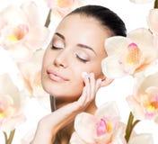 Donna che applica crema cosmetica sul fronte Fotografia Stock