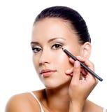 Donna che applica eyeliner sulla palpebra con il pensil immagine stock