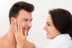 Donna che applica idratante sulla guancia dell'uomo Immagine Stock