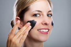 Donna che applica la maschera del carbone attivo sul suo fronte fotografie stock libere da diritti