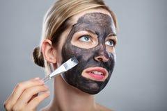 Donna che applica la maschera di protezione del carbone attivo con la spazzola fotografia stock libera da diritti