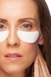 Donna che applica la mascherina di occhio del gel Immagini Stock