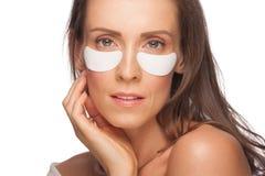 Donna che applica la mascherina di occhio del gel Fotografia Stock