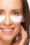 Donna che applica la mascherina di occhio del gel Fotografia Stock Libera da Diritti