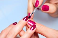 Donna che applica lo smalto per unghie alle unghie del dito Fotografia Stock