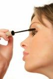 Donna che applica mascara Fotografie Stock Libere da Diritti