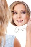 Donna che applica mascara Immagini Stock