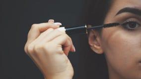 Donna che applica mascara nera sui cigli con la spazzola di trucco Giovane bella donna che applica trucco della mascara sugli occ video d archivio