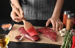 Donna che applica olio su bistecca cruda con la spazzola del silicone fotografia stock