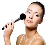 Donna che applica polvere sulla guancica con la spazzola fotografia stock