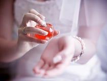 Donna che applica profumo sulla sua manopola Fotografie Stock