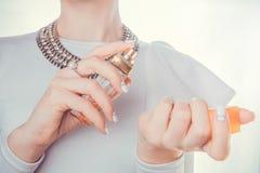 Donna che applica profumo sulla sua manopola Immagini Stock Libere da Diritti