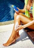 Donna che applica protezione solare sulle gambe Fotografia Stock Libera da Diritti