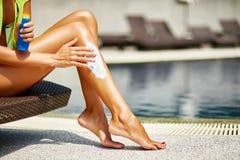 Donna che applica protezione solare sulle sue gambe abbronzate regolari Fotografia Stock Libera da Diritti