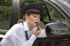 Donna che applica rossetto che guarda in specchietto retrovisore esterno dell'automobile Immagini Stock Libere da Diritti