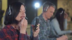 Donna che applica rossetto nella call center video d archivio