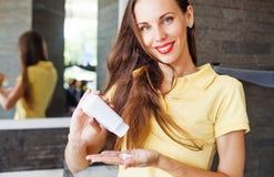 Donna che applica sciampo asciutto sui suoi capelli immagine stock