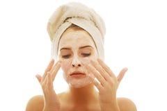 Donna che applica una crema sul suo fronte Immagini Stock