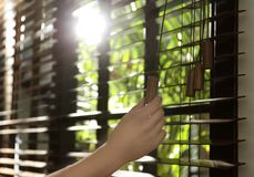 Donna che apre i ciechi di finestra orizzontali a casa immagini stock libere da diritti