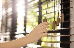 Donna che apre i ciechi di finestra orizzontali a casa fotografia stock libera da diritti