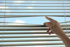 Donna che apre i ciechi di finestra orizzontali a casa, primo piano fotografia stock libera da diritti