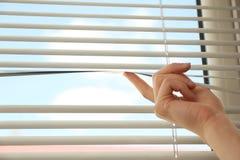 Donna che apre i ciechi di finestra orizzontali a casa, primo piano immagine stock libera da diritti