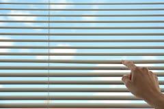 Donna che apre i ciechi di finestra orizzontali a casa, primo piano immagine stock